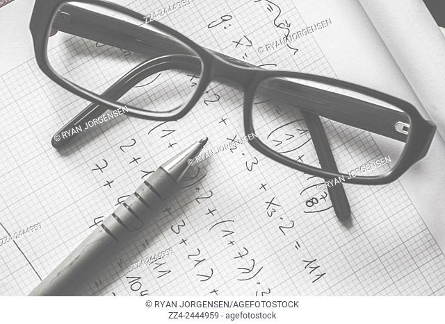 Black and white object photo of complex math formulas written on lined graph paper with pen and optical eye wear. Education smarts