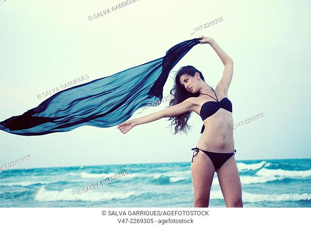Woman posing in black bikini on the beach with a scarf blowing in the wind