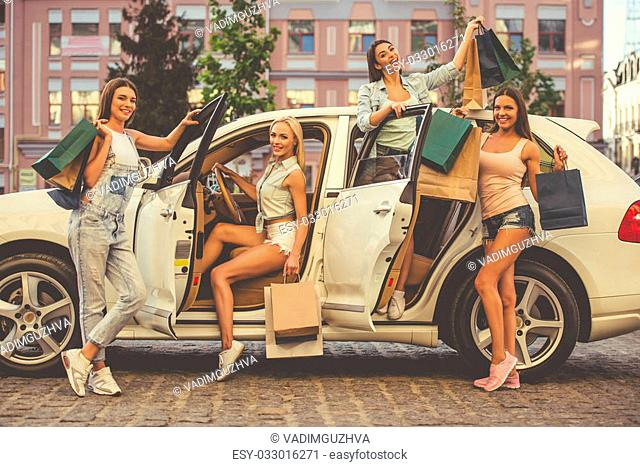 Beautiful stylish girls are holding shopping bags, looking at camera and smiling while sitting in and standing near their car outdoors