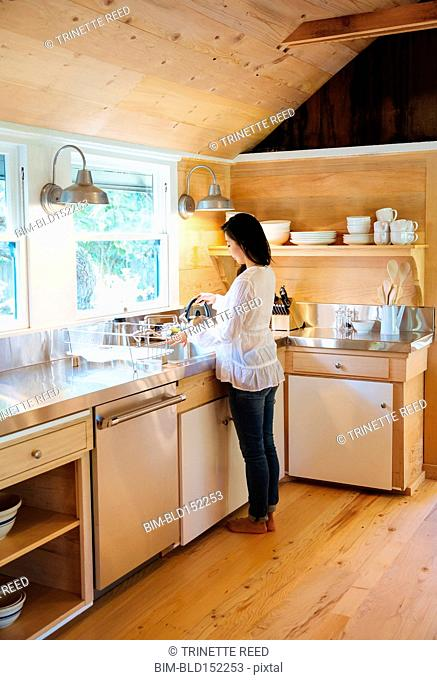 Chinese woman filling kettle in rustic kitchen