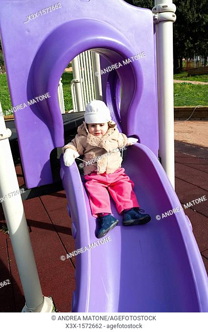 Little child playing on a playground slide