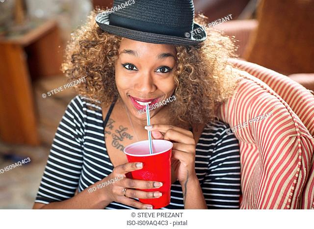 Portrait of young woman wearing fedora and drinking soft drink