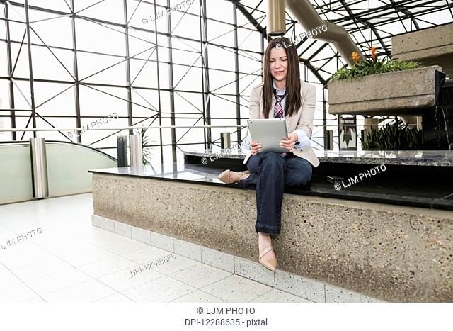 Mature business woman with a tablet in the atrium of an office building; Edmonton, Alberta, Canada
