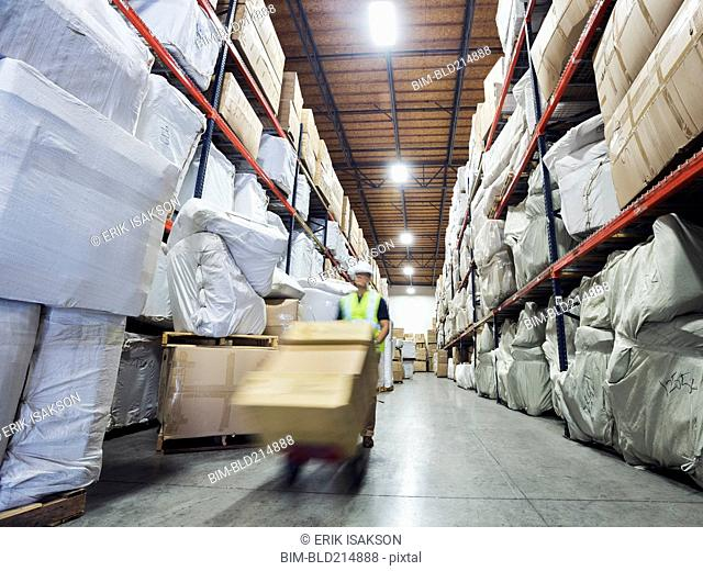 Blurred view of Caucasian worker wheeling cardboard box in warehouse