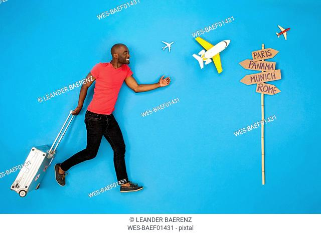 Man with suitcase hurrying to to get his flight for a city break