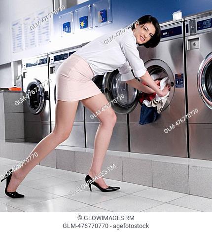 Woman putting clothes into a washing machine
