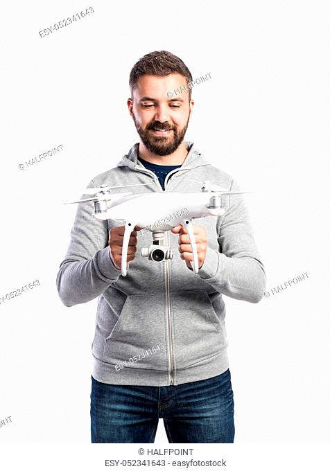 Young hipster man in gray sweatshirt holding drone with camera. Studio shot on white background, isolated