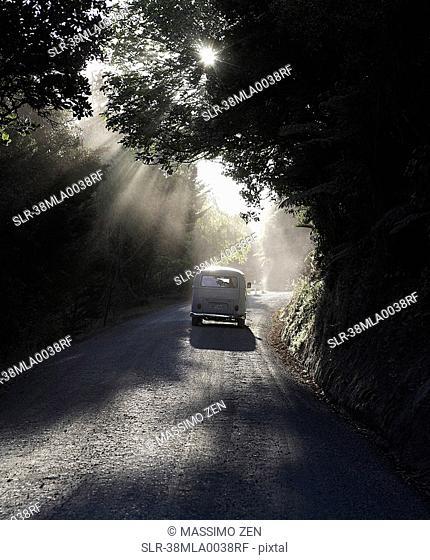 Car driving down rural road