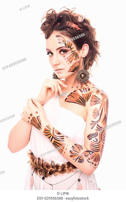 Beautiful lady with interesting bodyart posing in the image of Greek goddess. Serious lady with elegant make-up posing in photo studio