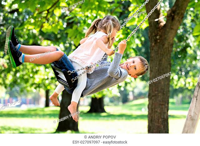 Happy Young Brother And Sister Sitting On Swing In The Park