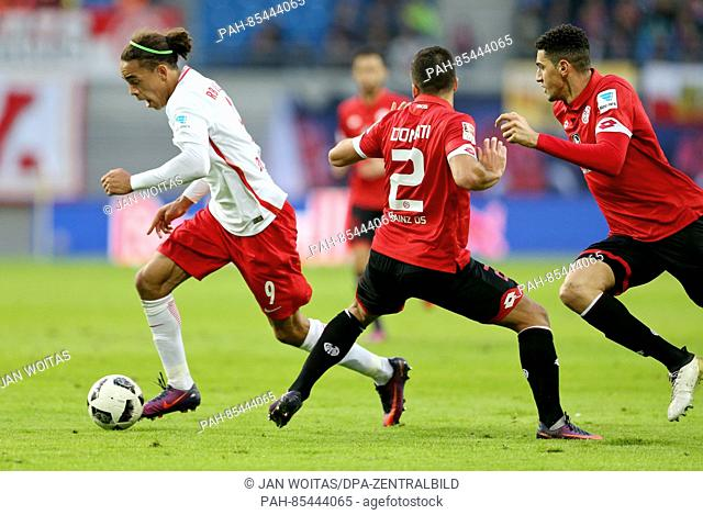 Leipzig's Yussuf Poulsen (l) and Mainz' Giulio Donati (c) and Leon Balogun in action during the Bundesliga soccer match between RB Leipzig and FSV Mainz 05 at...