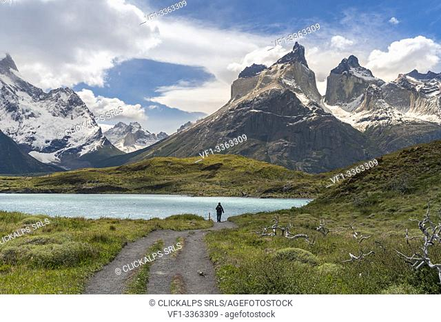 Woman walking on the footpath towards Mirador Cuernos, with Nordenskjold Lake and Paine Horns in the background, in summer