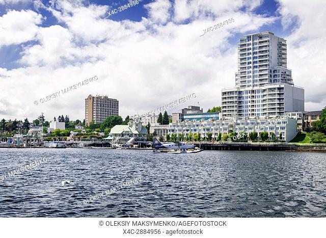 Fairmont Harbour Air seaplane in Nanaimo harbour with Nanaimo waterfront city skyline in the background. Vancouver Island, British Columbia, Canada 2017