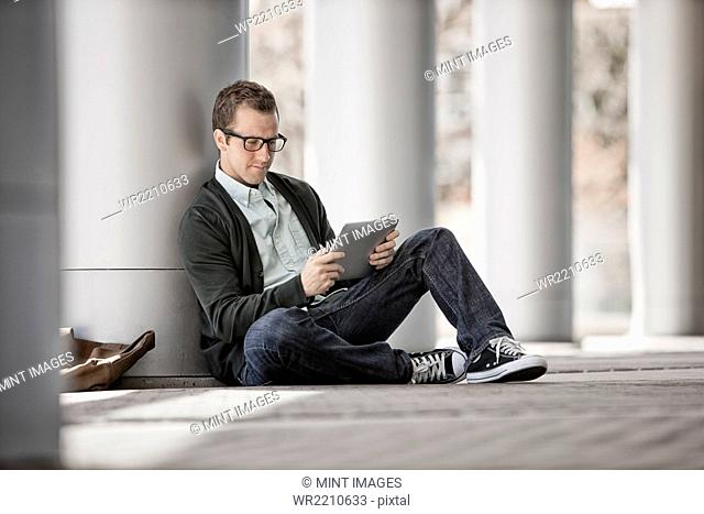 A man sitting leaning against a pillar using a digital tablet
