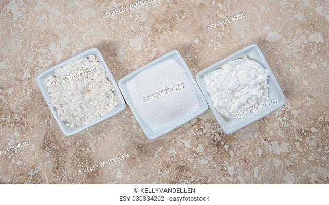 Flour, Sugar, and Corn Starch in Bowls on a travertine background