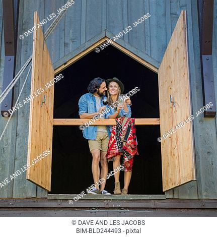 Hispanic couple hugging near open barn doors drinking wine