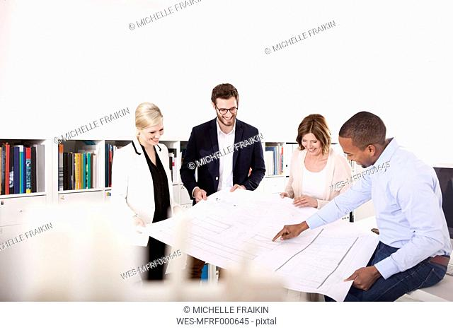 Four colleagues discussing construction plan in an office