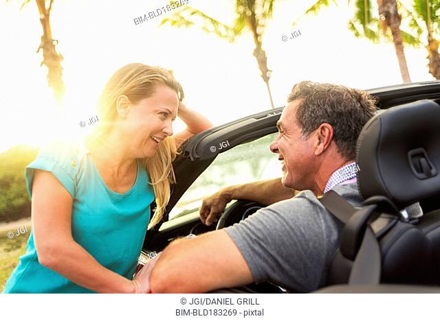 Caucasian talking in convertible