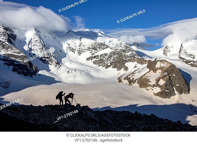 Photographers at Diavolezza Refuge, looking at Bernina glaciers. Diavolezza Refuge,Engadine, Canton of Graubunden,Switzerland Europe