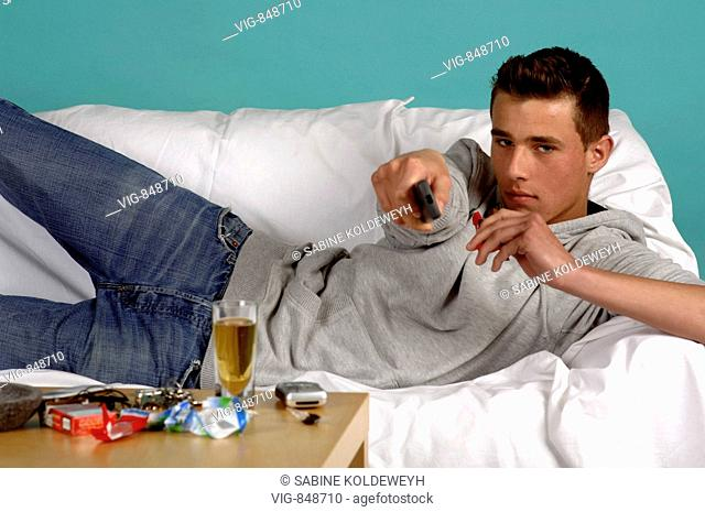 A young man is lying on the sofa while watching tv. - 30/05/2008