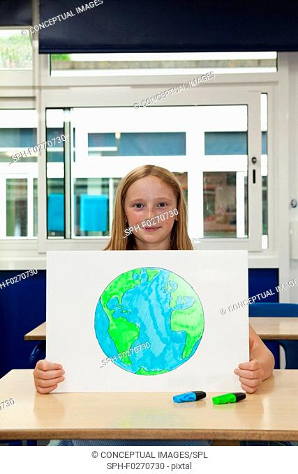 Girl holding up placard with a drawing of the Earth