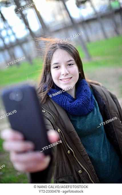 Cute teenager takes selfie in park