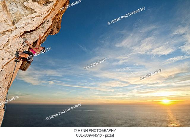 Female climber on steep sea cliff, climbing limestone at the Calanques, Route de Crete, Bouches-du-Rhone, France
