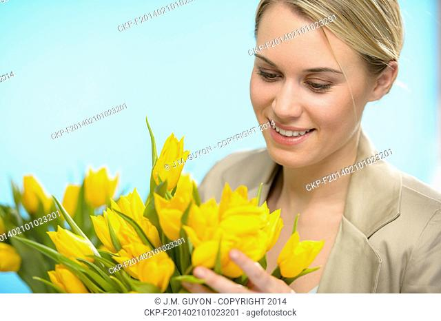 Woman looking down spring yellow flowers hold bouquet of tulip