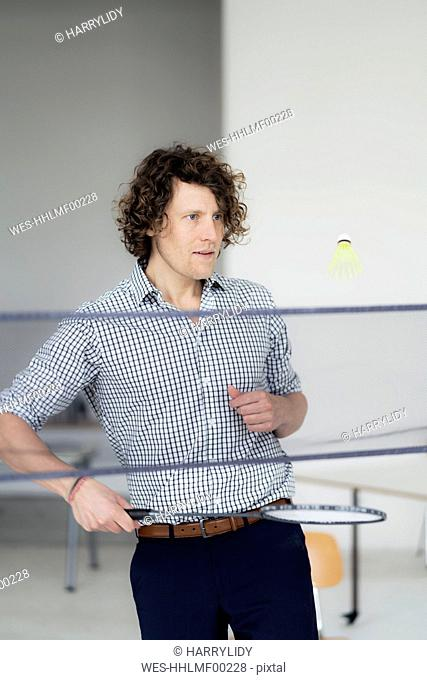 Businessman having fun in the office, playing with badminton racket and shuttlecock