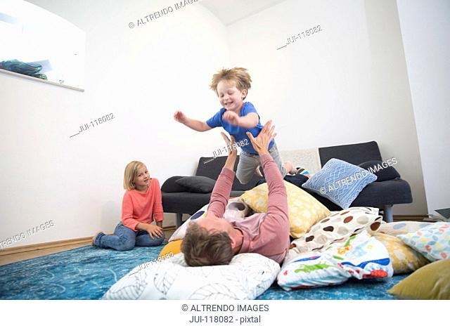 Children Jumping On Father As He Lies On Cushions At Home