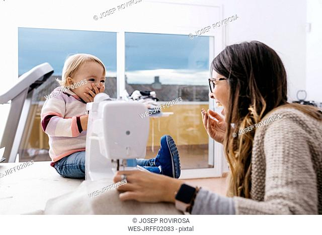 Happy mother with little daughter at home using sewing machine