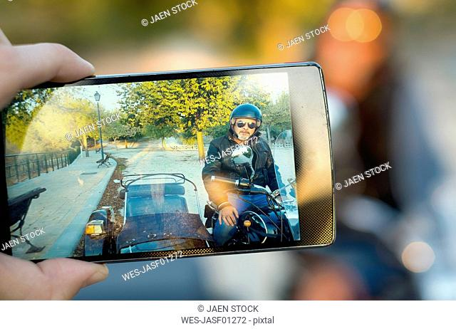 Man taking a photo of biker on his sidecar motorcycle, close-up