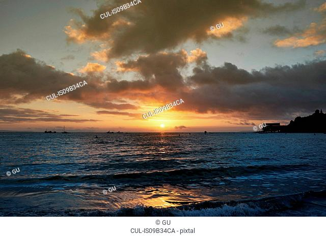 Silhouette of boats on sea at sunrise, Tenby, Pembrokeshire, Wales