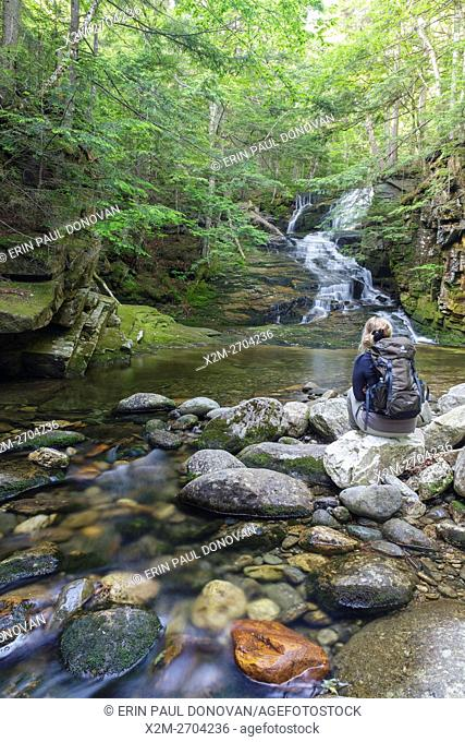 A female hiker sitting in from of Tama Falls on Snyder Brook in Randolph, New Hampshire during the summer months. This waterfall is located along the Fallsway...
