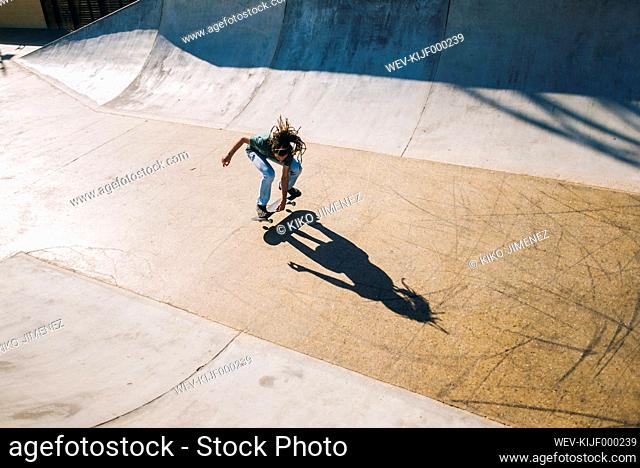 Young man with dreadlocks skateboarding in a skatepark