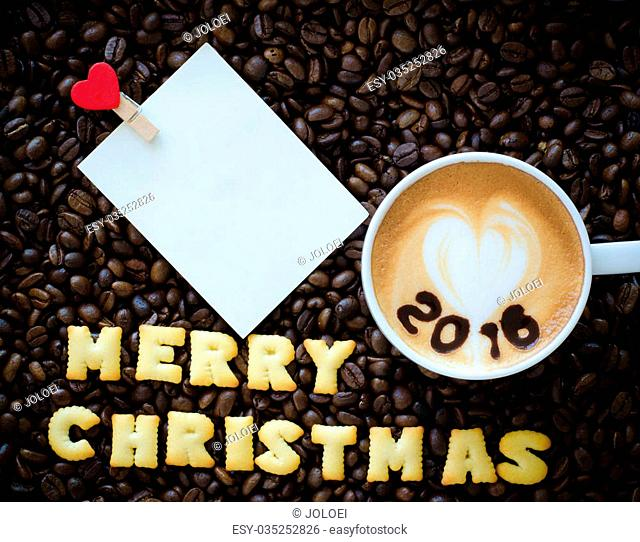 """latte art coffee and alphabet """"""""merry christmas"""""""" made from bread cookies on coffee beans background"""