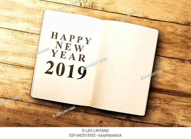 Opened book with new year message and empty space for copyspace on wooden table. Happy New Year 2019