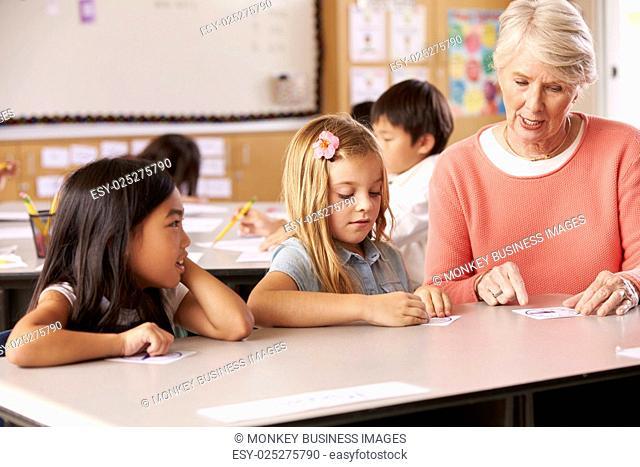Senior teacher helping pupils in elementary school lesson