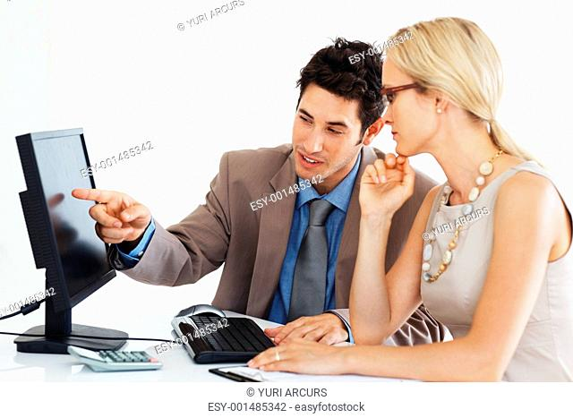 Young business man with female colleague pointing at computer screen while preparing project