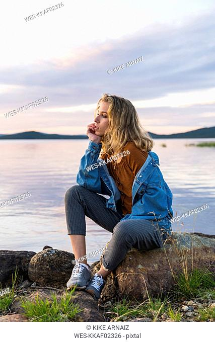 Finland, Lapland, young woman sitting on a rock at the lakeside
