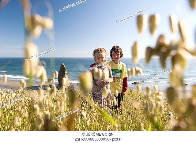 Children standing in wildlowers growing near beach