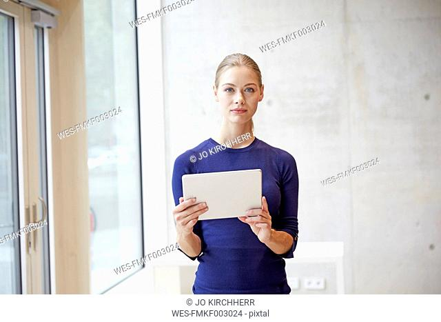 Portrait of young woman holding tablet