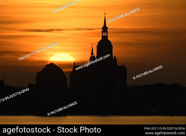 13 November 2020, Mecklenburg-Western Pomerania, Stralsund: Orange is the sky at sunset over the silhouette of the Hanseatic city of Stralsund with St