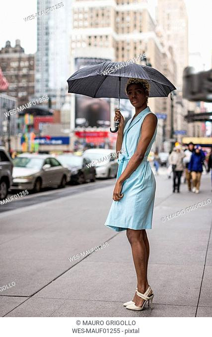 USA, New York, young blonde african-american woman with umbrella