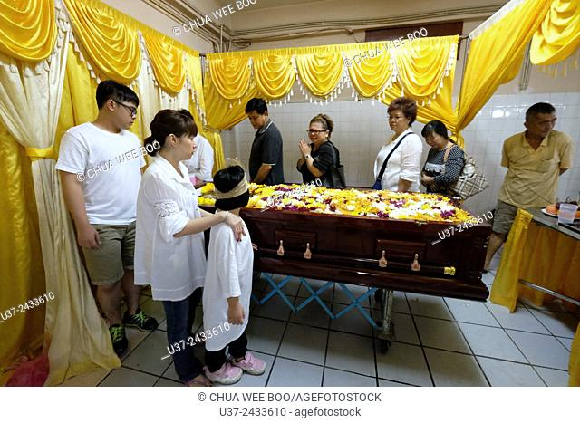 Relatives strolling in circle and prayers for the deceased. Sarawakian chinese funeral ceremony. Malaysia