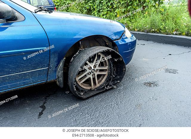 A badly damaged front tire coming off of a wheel of a parked car