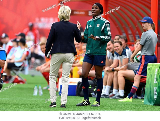 Germany's head coach Silvia Neid (L) speaks with 4th official Gladys Lengwe during the FIFA Women's World Cup 2015 third place soccer match between England and...