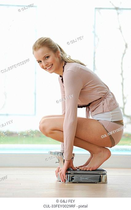 Woman crouching on bathroom scale
