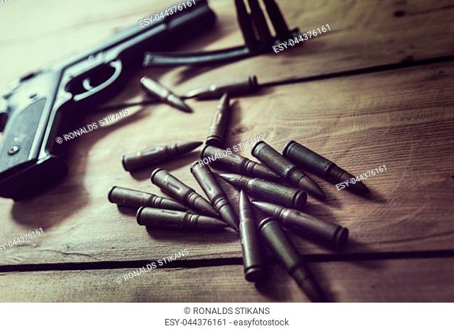 gun and ammunition on wooden table