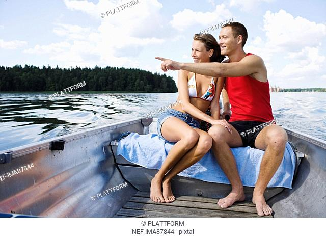 Young couple in motorboat on lake